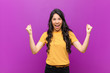canvas print picture - young pretty latin woman feeling happy, surprised and proud, shouting and celebrating success with a big smile against purple wall