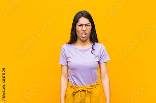 Fotografie, Tablou  young pretty latin woman feeling disgusted and irritated, sticking tongue out, d