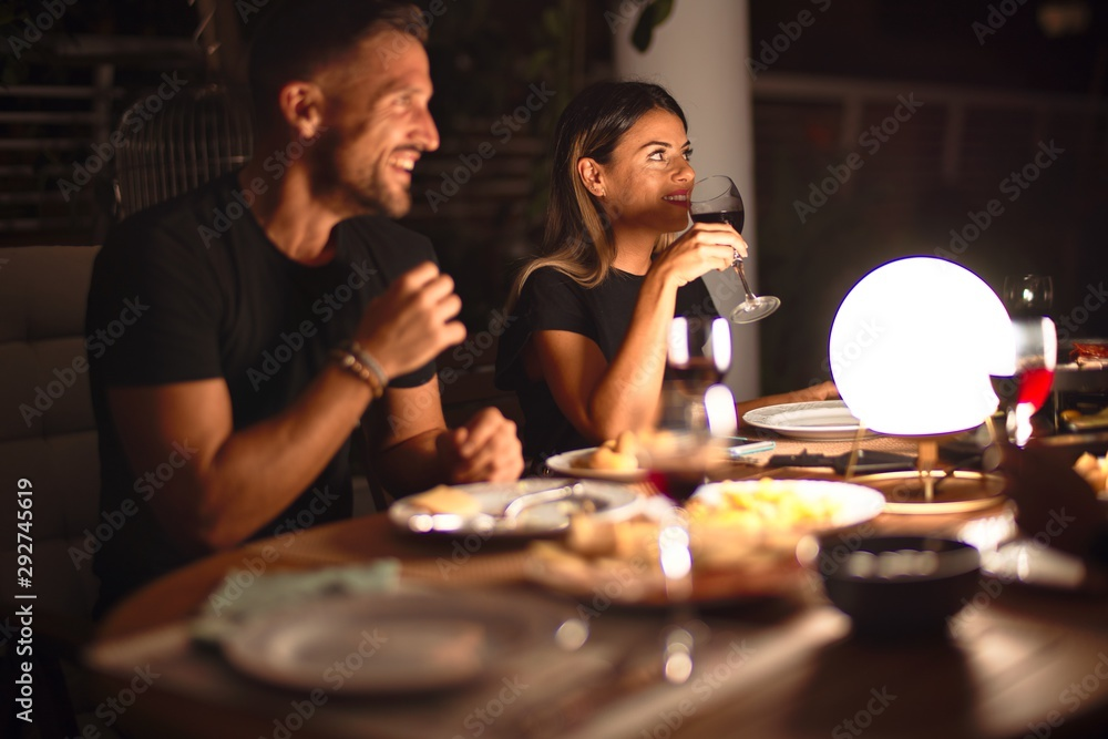 Fototapeta Young beautiful couple dinning and smiling on celebration at terrace