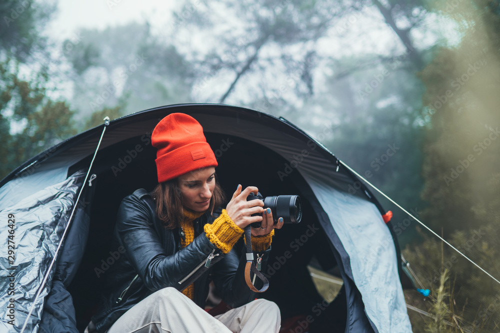 Fototapety, obrazy: photographer tourist traveler take photo on camera in camp tent in foggy rain forest, hiker woman shooting mist nature trip, green trekking tourism, rest vacation concept camping holiday