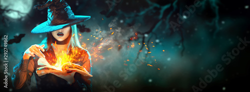 Halloween Witch girl with magic Book of spells portrait. Beautiful young woman in witches hat conjuring, making witchcraft. Over spooky dark magic forest background. Wide Halloween party art design. - 292749862