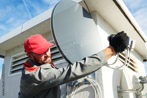 Service worker installing and fitting satellite antenna dish for cable TV Wallpaper Mural