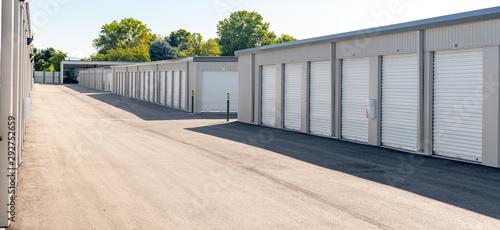 Fotografie, Obraz Mini garages of a storage unit facility with trees