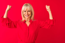 Middle Age Woman Wearing Elegant Shirt Standing Over Isolated Red Background Showing Arms Muscles Smiling Proud. Fitness Concept.