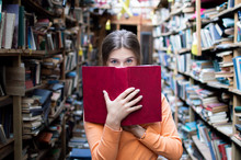 Girl Student Reads A Big Red Book In The Library And Looks At The Camera, She Has Blue Eyes, Close-up