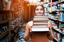 Girl Student Holds A Stack Of Books In The Library, She Searches For Literature And Offers To Read, A Woman Prepares For Study, Knowledge Is Power, Bookseller On The Background Of The Bookstore