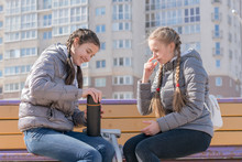 Traveler Teenager Girl And Friend Opening Thermos With Tea Outdoors
