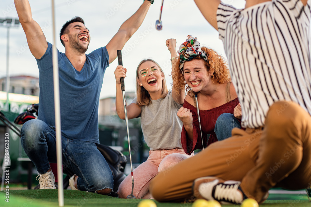 Fototapety, obrazy: Group of smiling friends enjoying together playing mini golf in the city.
