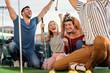 Leinwandbild Motiv Group of smiling friends enjoying together playing mini golf in the city.