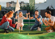 canvas print picture - Group of smiling friends enjoying together playing mini golf in the city.