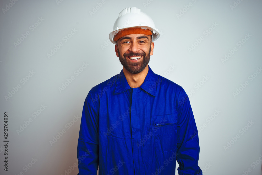 Fototapeta Handsome indian worker man wearing uniform and helmet over isolated white background with a happy and cool smile on face. Lucky person.