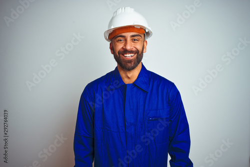 Obraz Handsome indian worker man wearing uniform and helmet over isolated white background with a happy and cool smile on face. Lucky person. - fototapety do salonu