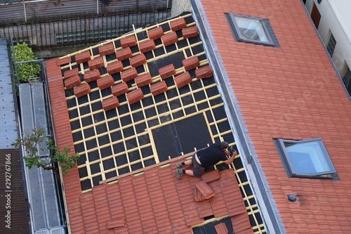 Fototapeta Couvreur posant des tuiles sur le toit d'une maison obraz