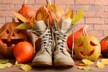 Boots, Halloween Pumpkins And Autumn Leaves Near Brick Wall