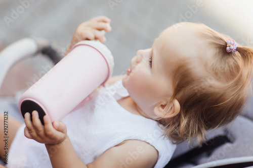 Small pretty girl sitting in a stroller and drinking water or milk from her thermos, baby for a walk in a pram, child in summer outdoors Wallpaper Mural