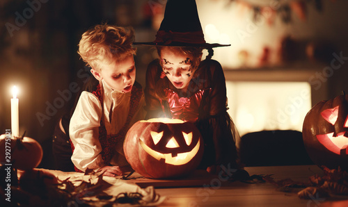happy children in costumes of witch and vampire in a dark house in halloween. - 292775021