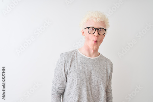 Fototapeta Young albino blond man wearing striped t-shirt and glasses over isolated white background making fish face with lips, crazy and comical gesture