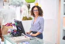 Middle Age Beautiful Clothes Shop Owner Woman Smiling Happy And Confident Working With Computer At Counter