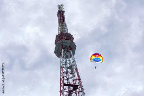 Photo Parachutists jumping down from a big antenna
