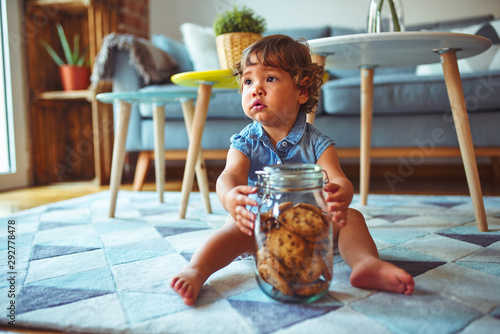 Fototapeta Beautiful toddler child girl holding jar of cookies sitting on the floor
