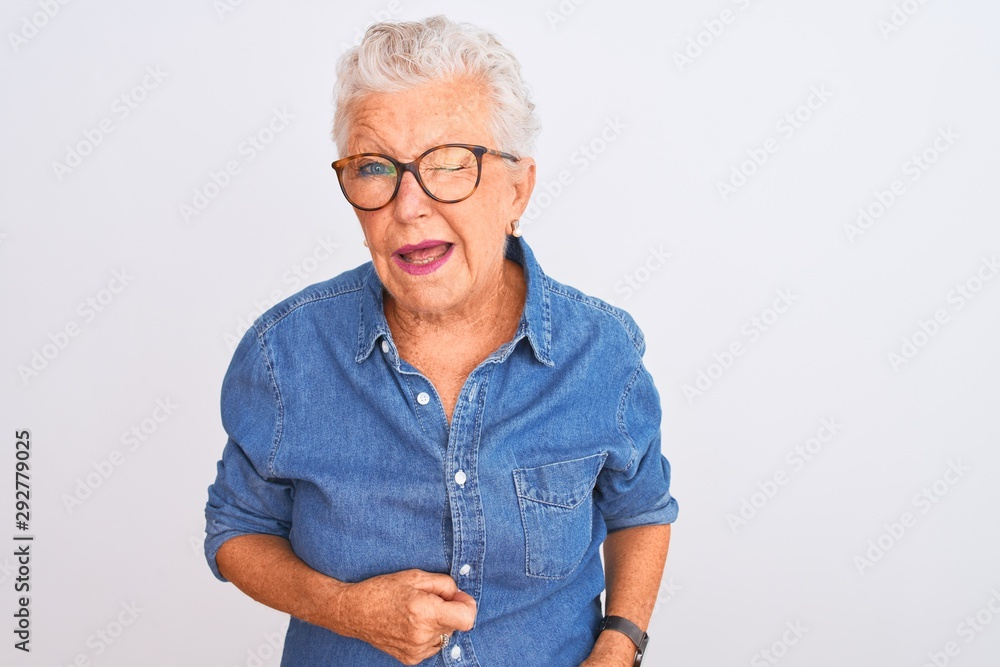 Fototapeta Senior grey-haired woman wearing denim shirt and glasses over isolated white background winking looking at the camera with sexy expression, cheerful and happy face.