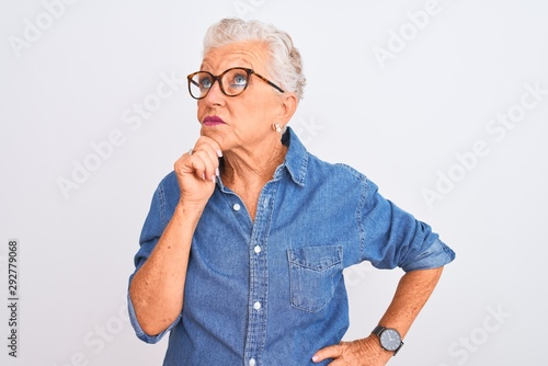 Senior grey-haired woman wearing denim shirt and glasses over isolated white background with hand on chin thinking about question, pensive expression Fototapet