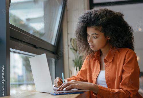 Student using laptop computer, studying, learning language, exam preparation in modern library. Pensive African American woman freelancer writes notes, planning working process at workplace