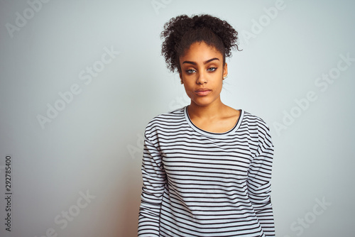 Obraz African american woman wearing navy striped t-shirt standing over isolated white background looking sleepy and tired, exhausted for fatigue and hangover, lazy eyes in the morning. - fototapety do salonu