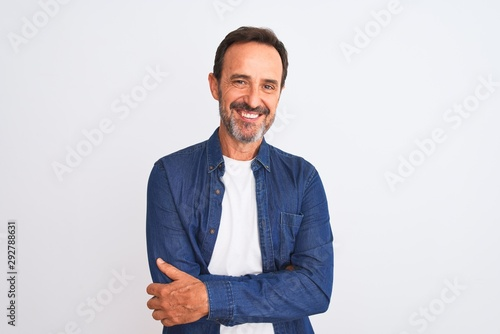 Photo  Middle age handsome man wearing blue denim shirt standing over isolated white background happy face smiling with crossed arms looking at the camera