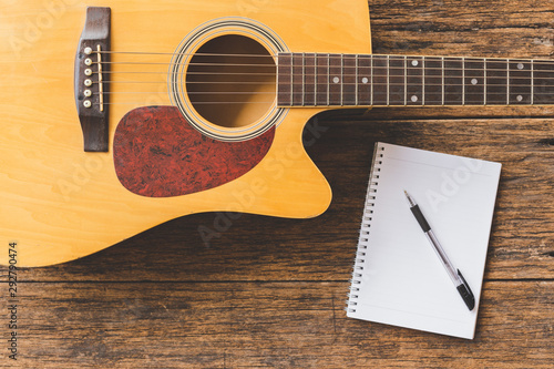 Top view of Acoustic guitar , Notebook paper and pen on wood background  and cop Canvas Print
