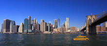 Lower Manhattan Skyline, Eastern River And Brooklyn Bridge With A Yellow Water Taxi Boat On The Foreground, New York City