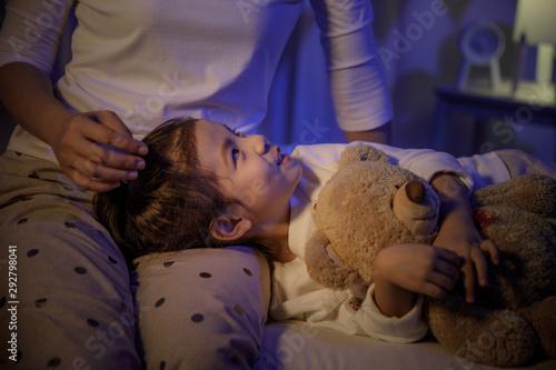 Fotografia  Mother stroking head of cute girl then sleeping on mom lap on bed in a dark bedr