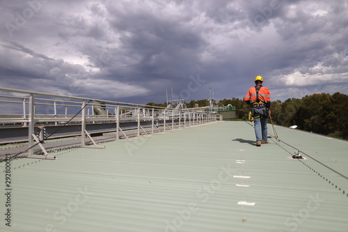 Fotografiet Construction safety inspector wearing fall safety harness walking on the roof by
