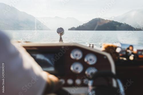 Widok na jezioro Como przez okno jachtu. Sylwetki wzgórz na horyzoncie. Luksusowe wakacje i rejs statkiem. Wycieczka łodzią. Jachting we Włoszech.