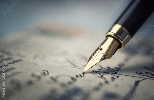 Old fountain pen on an vintage handwritten letter. Conceptual background on history, education, literature topics. Retro style.