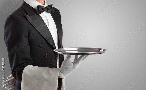Fotografie, Obraz Waiter serving with white gloves and steel tray in an empty space