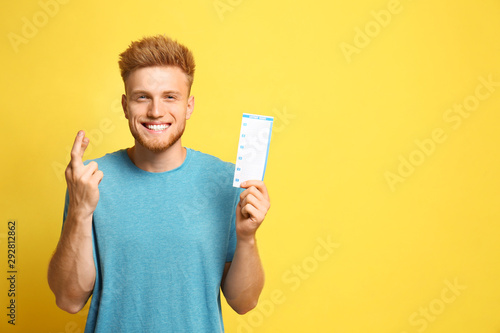 Fotomural Portrait of hopeful young man with crossed fingers holding lottery ticket on yel