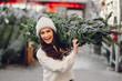 Leinwanddruck Bild - Elegant girl buys a Christmas tree. Woman in a white knited sweater. Beautiful lady with dark hair.