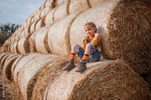 Fotografie, Tablou Cute girl having fun on rolls of hay bales in field