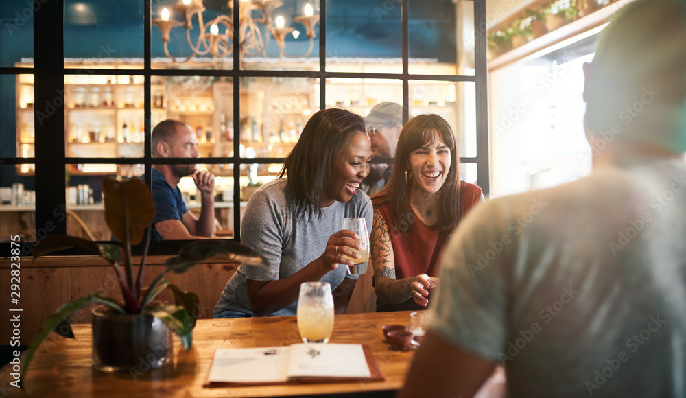 Fototapeta Diverse young friends laughing over drinks together in a bar