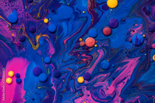 Obraz Acrylic paint balls abstract texture. Pink, blue and yellow liquids mix. Creative multicolor background. Bright colors fluid, flowing wallpaper design. Mixed pigments blue backdrop. - fototapety do salonu