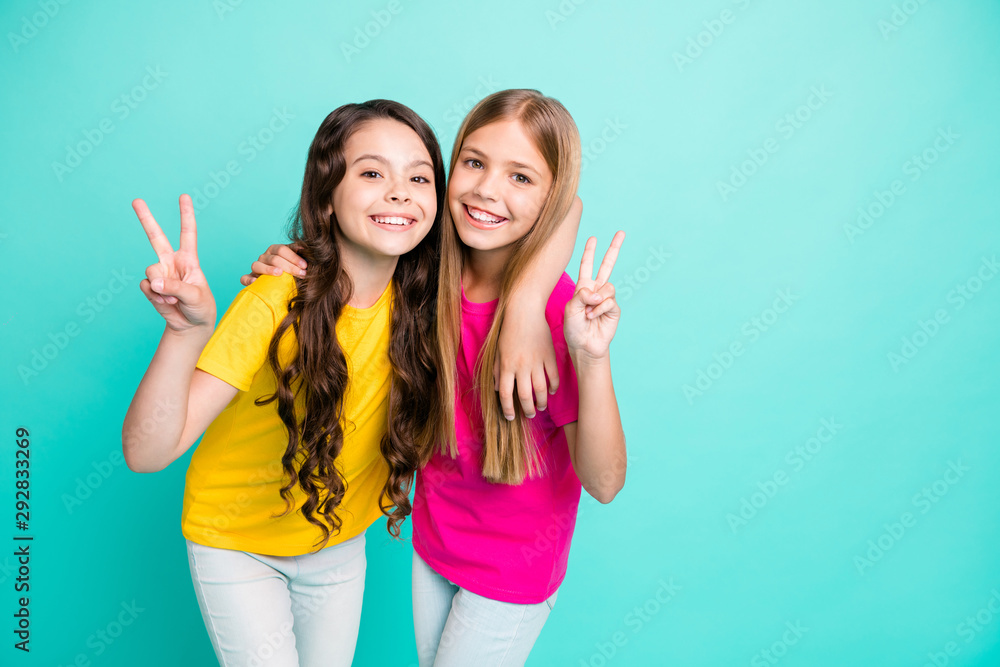 Fototapeta Photo of two excited cheerful nice cute girls showing you v-sign while isolated with teal background
