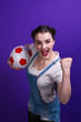 canvas print picture - Joyful woman holding a soccer ball over isolated blue wall at studio