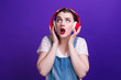 canvas print picture - Cheerful girl listen to music in big red headphones isolated at blue background on studio.