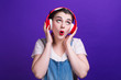 canvas print picture - Funny girl singing in big red headphones isolated at blue background on studio.