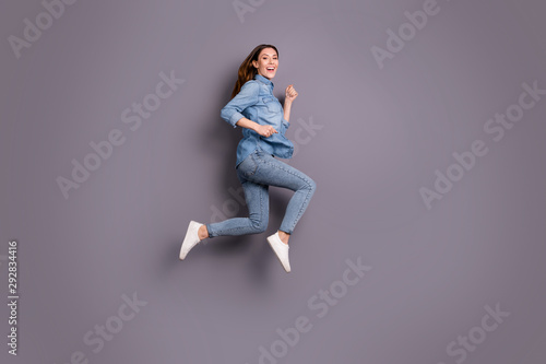 Fototapeta Full length profile photo of pretty lady jumping high running to attend sale in shopping center wear casual jeans outfit isolated grey background obraz na płótnie