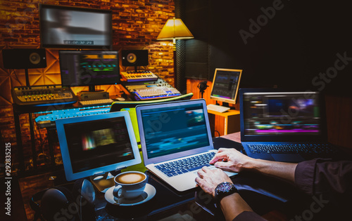 professional director, editor, producer editing movie footage and music score track on computer in digital editing, post production, broadcasting studio - 292835215