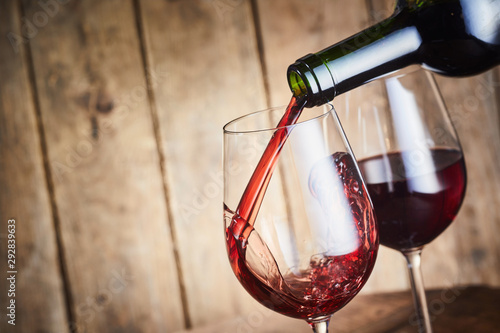 Photo sur Toile Pays d Afrique A glass of dry red wine being poured from a bottle