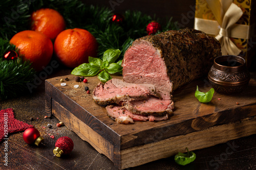 Juicy roast beef with spices sliced on cutting Board, delicious meat, traditional food. Christmas holidays, new year, menu on dark background - 292840031