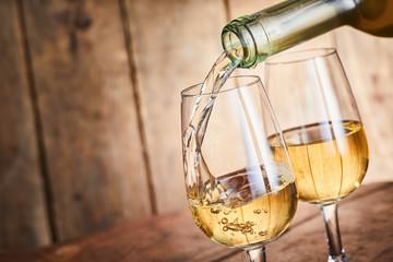 Dispensing golden white wine into two wineglasses
